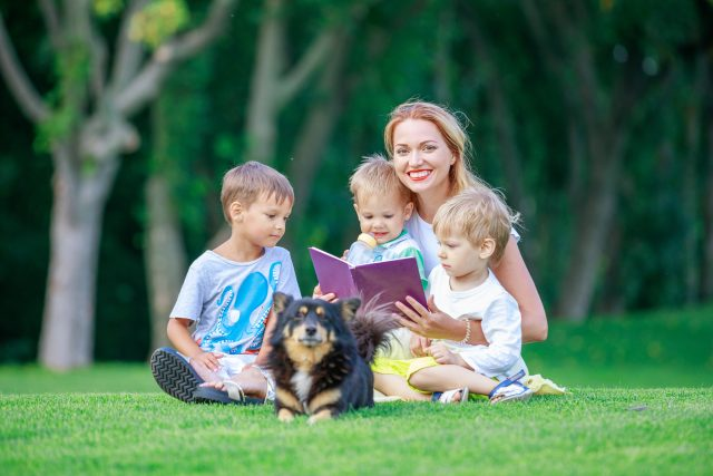 mom and kids read book with a dog